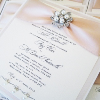 Beautiful vintage designed wedding invitations with pearl brooches