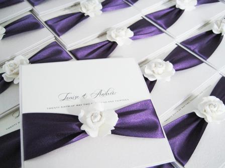 Rose wedding invitations with purple ribbon
