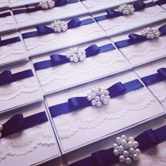 Lace and pearl wedding invitations with navy blue ribbon