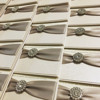 Silver grey and ivory boxed wedding invitations with crystal brooch