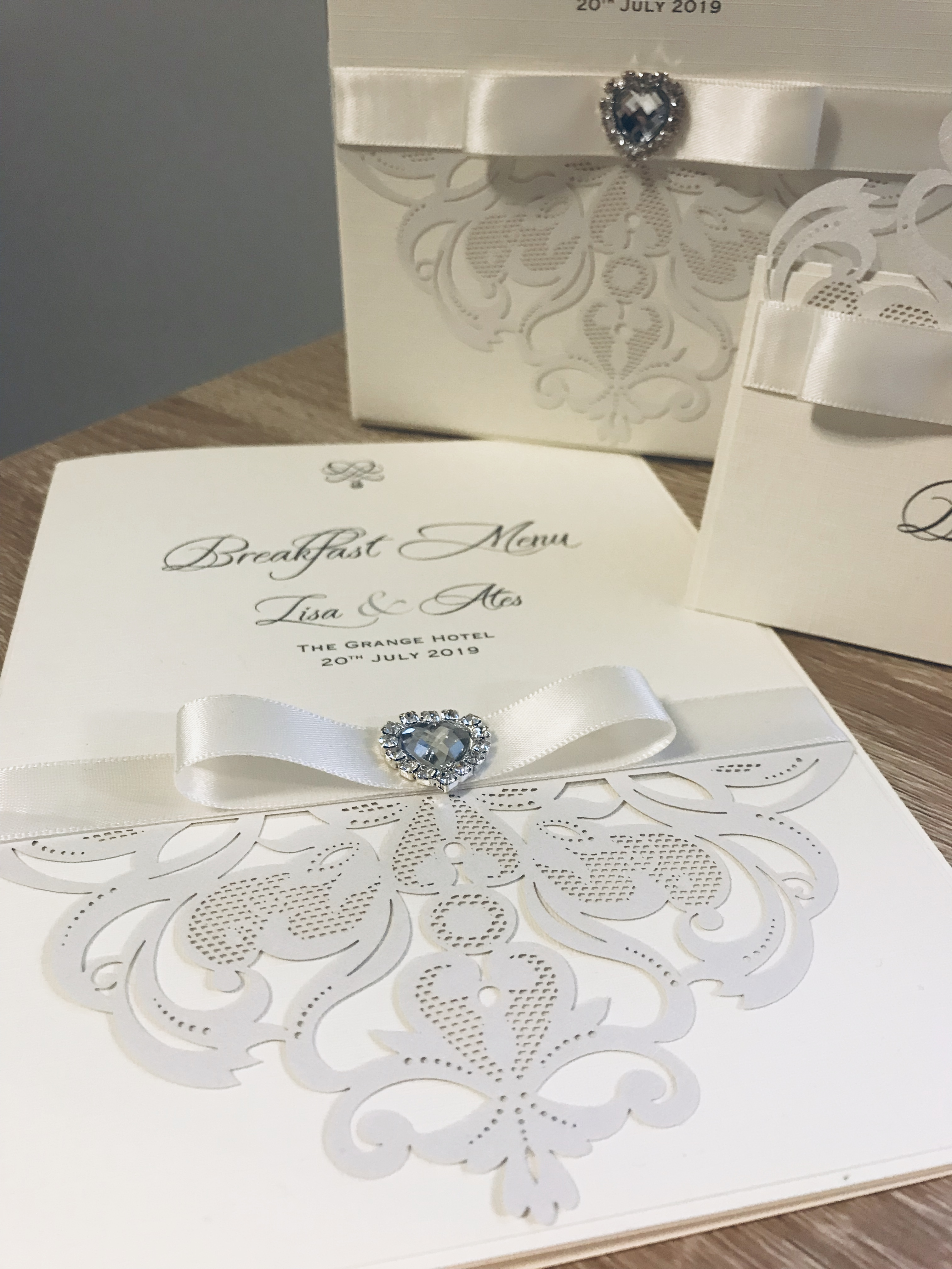 Luxury wedding breakfast menus decorated with crystal heart brooch and laser detail