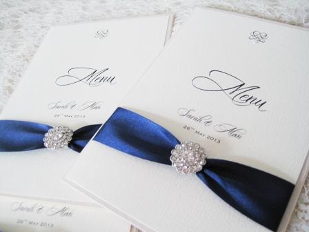 beautiful crystal wedding breakfast menu with navy blue ribbon and vintage brooch